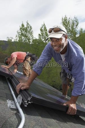 pracownicy budowlani instaluje panel sloneczny na