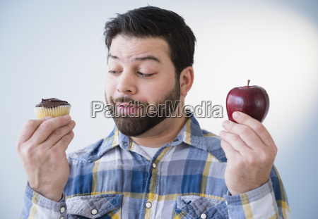 portrait of uncertain man holding apple
