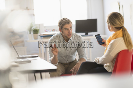 young man and woman discussing at
