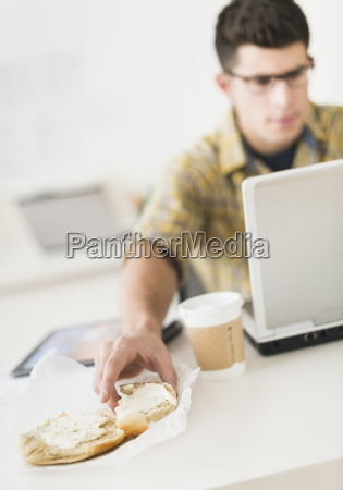young man eating sandwich and using