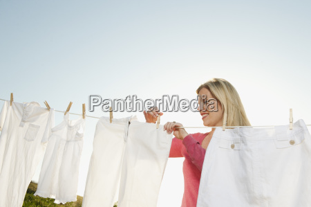 woman hanging laundry on clothesline