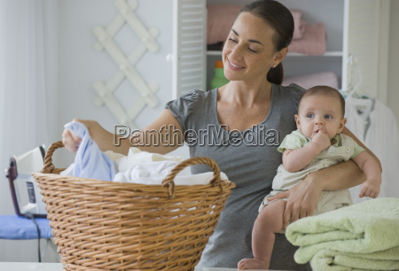 mother holding baby son and sorting
