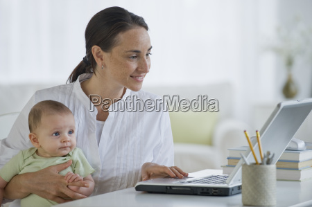 mother working on laptop and holding