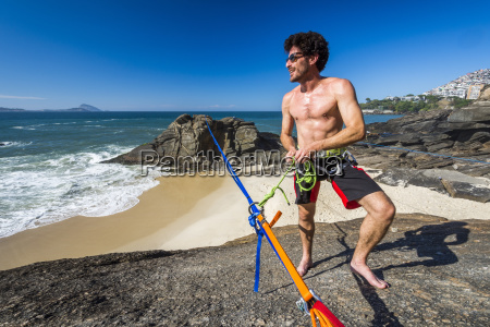 man tying himself to slackline at