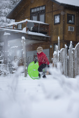 young boy carrying plastic sled across