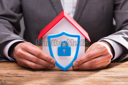 businessperson holding shield security icon on