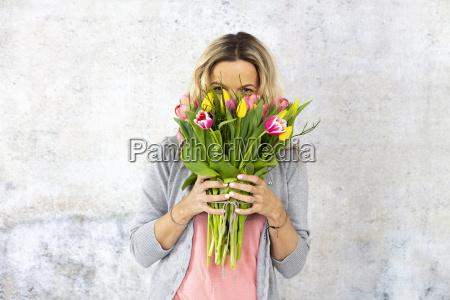 mloda ladna kobieta z bukietem kwiatow