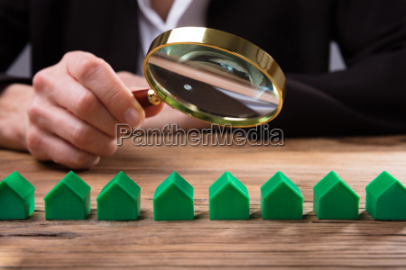 businessperson holding magnifying glass over house