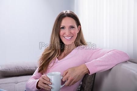 szczesliwa kobieta siedzi na kanapie holding