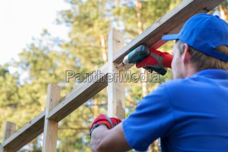 pracownik budowlany pracujacy na drewnianej strukturze