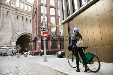 woman walking with bicycle on sidewalk