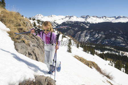 girl carrying skis in mountains silverton
