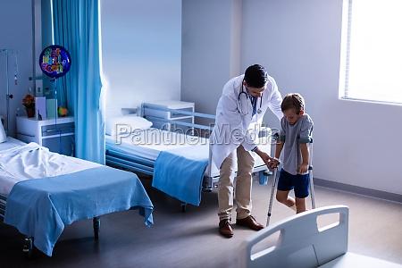 lekarz pomagajacy poszkodowanym chlopcu chodzic z