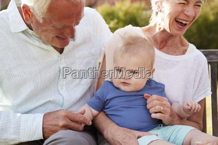 dziadkowie siedzi na miejscu w ogrodzie