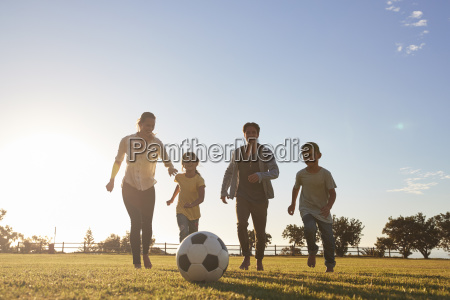 young family running after a football