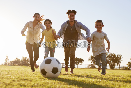 young family chasing after a football
