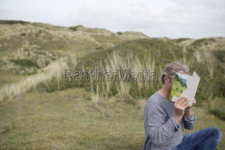 czlowiek czytajacy historie ksiazki na wydmach