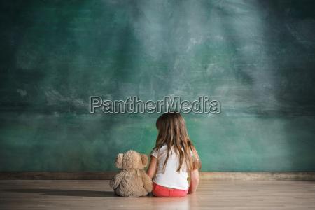 mala dziewczynka z misia siedzi na