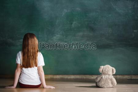 mala dziewczynka z pluszowym misiem siedzi