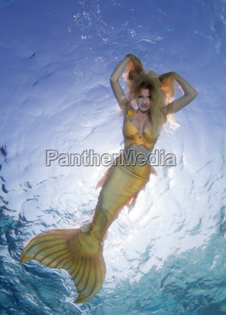 golden haired mermaid swims under the
