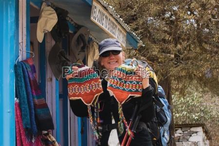 kobieta kupuje welniane kapelusze od sklepu
