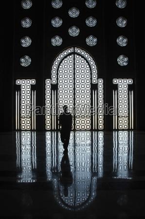 sylwetka osoby stojacej przed ozdobna sciana