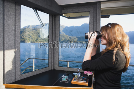 kobieta postrzega fiordow przez lornetke na