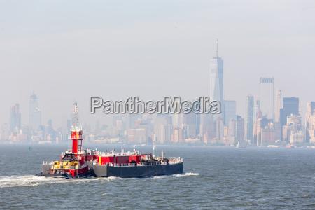 freight tug pushing cargo ship to