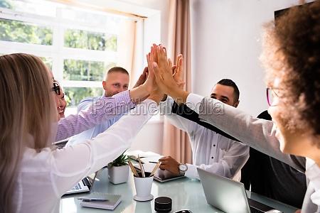 grupa biznesmenow dajaca piatke