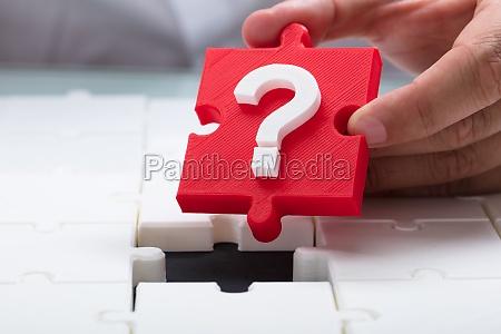 person placing question mark piece into