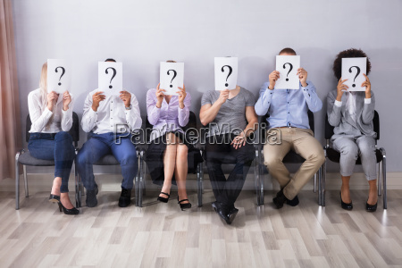 people holding question mark sign