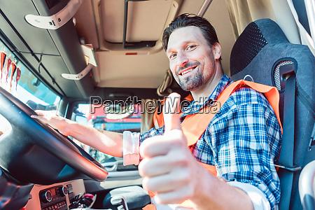 kierowca ciezarowki siedzi w kabinie dajac
