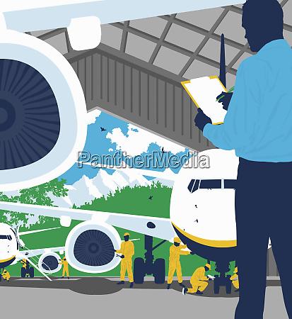 inzynier ze schowkiem nadzorujacy mechanike samolotu