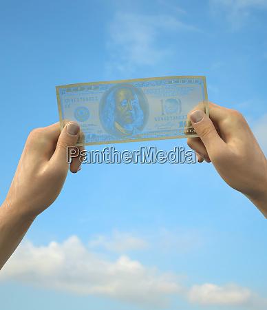 hands holding transparent one hundred dollar
