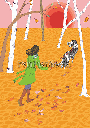 woman walking dog through autumn leaves