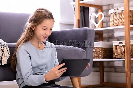 girl sitting on carpet using digital