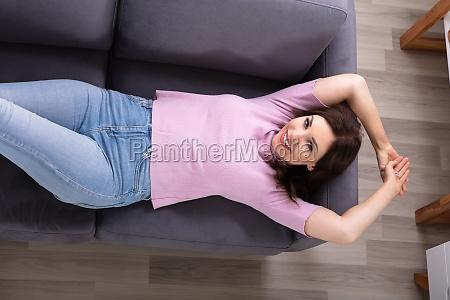 mloda kobieta lezac na kanapie