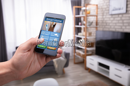 man holding cellphone with smart home