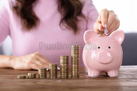 kobieta wstawianie monety w piggybank w