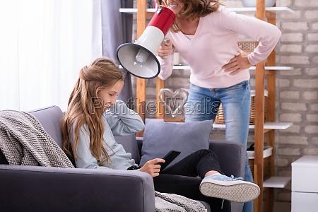 mother shouting through megaphone at girl