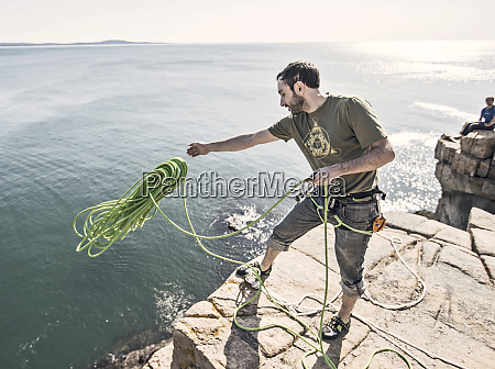man throwing rope as climbers preparing