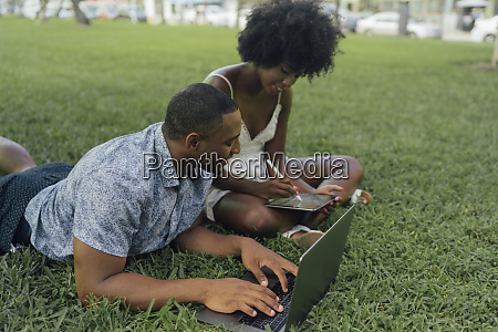 young couple using tablet and laptop