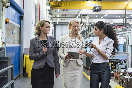 three women with tablet talking in