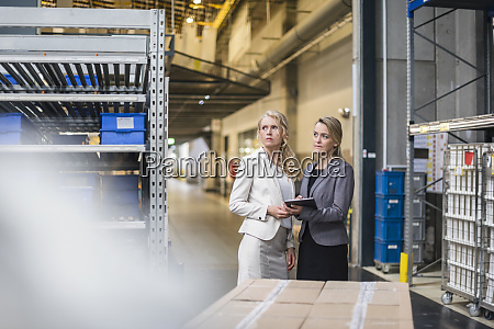 two women with tablet in factory