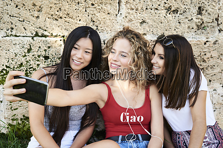 three smiling young women sitting at