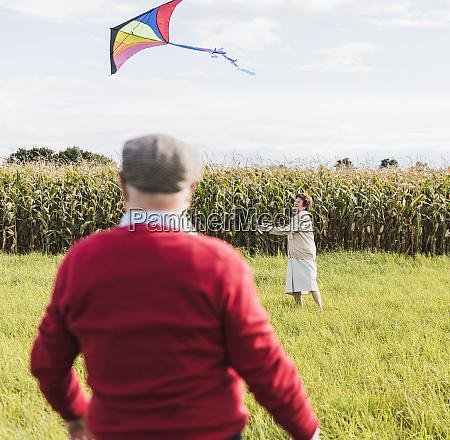 senior couple flying kite in rural