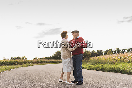 senior couple dancing on country road