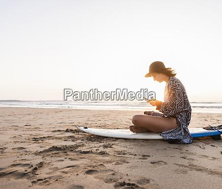 mloda kobieta siedzaca na desce surfingowej