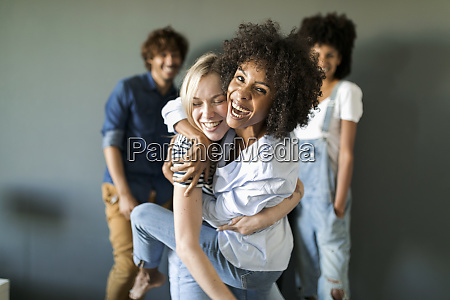 two happy women hugging with friends