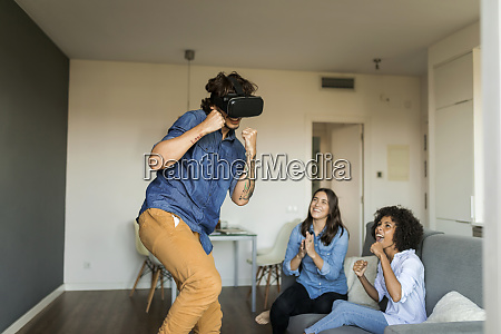 two women encouraging man gaming with